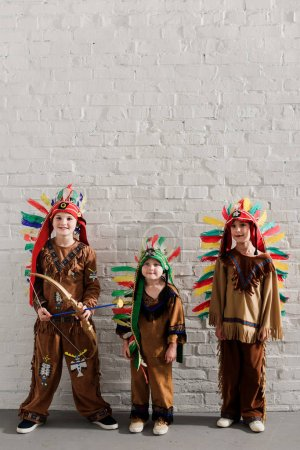 cute little boys in indigenous costumes standing against white brick wall