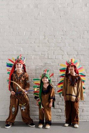 Niedliche kleine Jungen in indigenen Kostümen stehen vor weißen Ziegelwänden