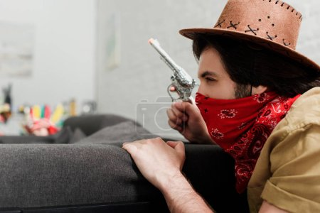 side view of man in red bandana and cowboy hat with toy gun at sofa at home