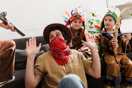 man in hat and red bandana playing together with sons in indigenous costumes at home