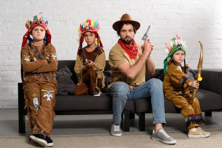 father in hat and red bandana sitting on sofa with little sons in indigenous costumes at home