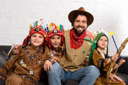 smiling father in hat and red bandana sitting on sofa with little sons in indigenous costumes at home