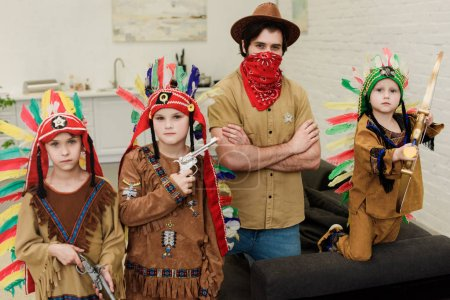portrait of little boys in indigenous costumes and father in hat and red bandana looking at camera at home