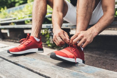 cropped image of sportsman tying shoelaces while sitting on bench at sport playground