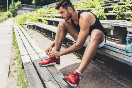 side view of sportsman tying shoelaces while sitting on bench at sport playground