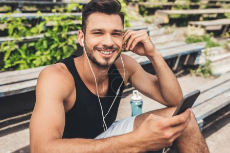 handsome young man listening music with smartphone and earphones on bench