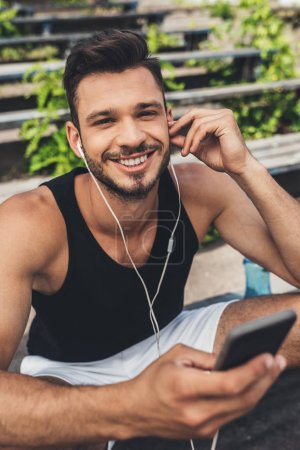 portrait of happy young sportsman listening music with smartphone and earphones