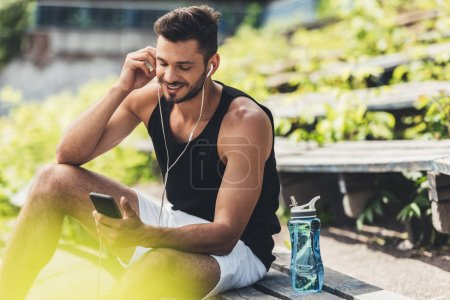 happy sportsman with bottle of water listening music with smartphone and earphones on bench at sport playground