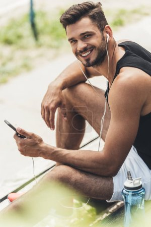 Photo for Young smiling man with bottle of water listening music with smartphone and earphones on bench - Royalty Free Image
