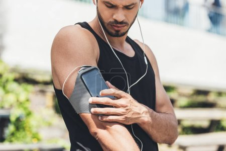 serious young sportsman in earphones with smartphone in running armband case