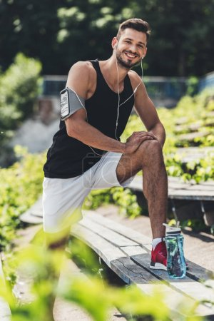 happy sportsman in earphones with smartphone in running armband case doing exercise on bench at sport playground