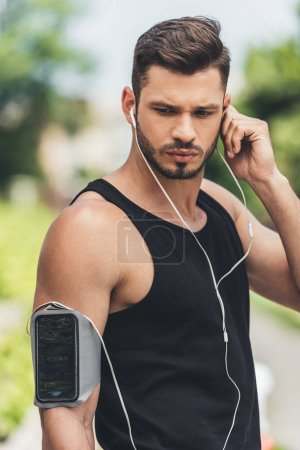 young sportsman in earphones with smartphone in running armband case