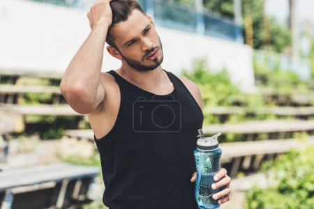 Photo for Front view of young sportsman holding bottle of water - Royalty Free Image
