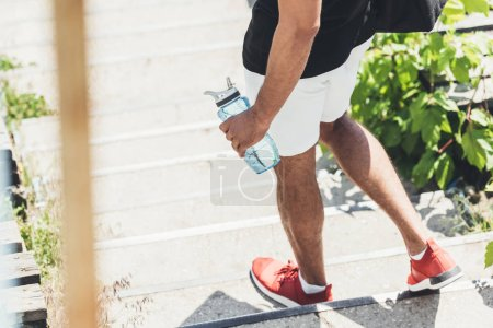 Photo for Cropped image of sportsman holding bottle of water on stairs at sport playground - Royalty Free Image