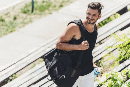 smiling sportsman holding bottle of water and bag for sport equipment on stairs at sport playground