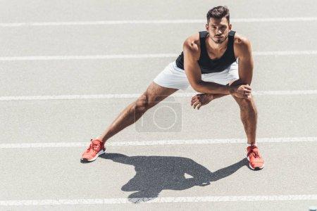 Photo pour Athlète masculin faisant de l'exercice sur piste de course au terrain de jeu sportif - image libre de droit