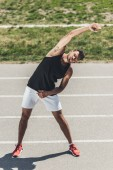 male athlete exercising on running track at sport playground