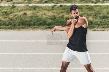 handsome young sportsman stretching on running track at sport playground