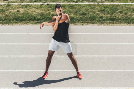 male athlete stretching on running track at sport playground