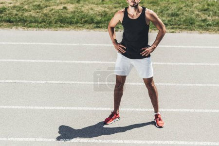 cropped image of male athlete standing on running track with arms akimbo