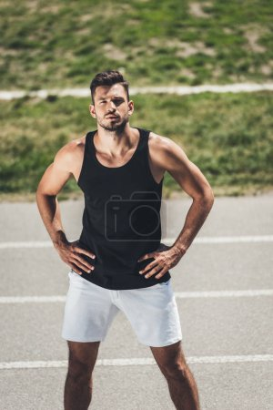 young sportsman standing on running track with arms akimbo