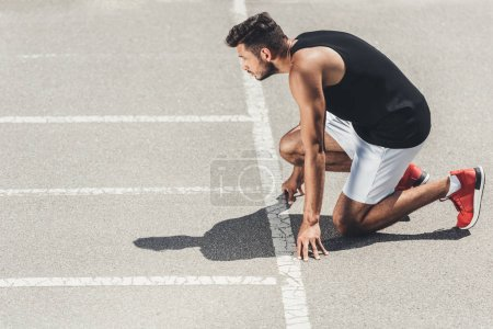side view of young male athlete on low start on running track