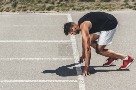 Photo for Serious young male athlete on low start on running track - Royalty Free Image