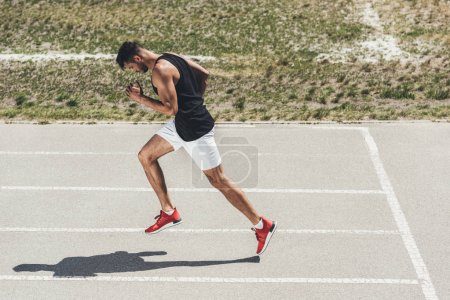 side view of male sprinter running on athletic track at sport playground