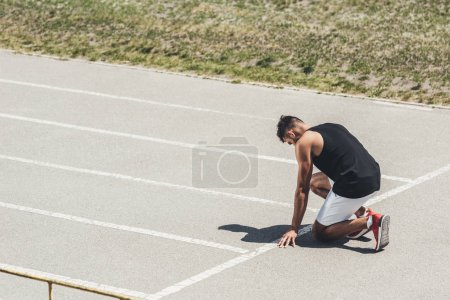 Photo for Side view of male sprinter in starting position on running track - Royalty Free Image