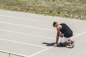side view of male sprinter in starting position on running track