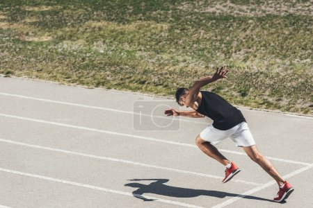 Photo for Young male sprinter taking off from starting position on running track - Royalty Free Image
