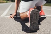 close up view of running shoes of male sprinter in starting position on running track