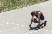young sportsman in starting position on running track at sport playground