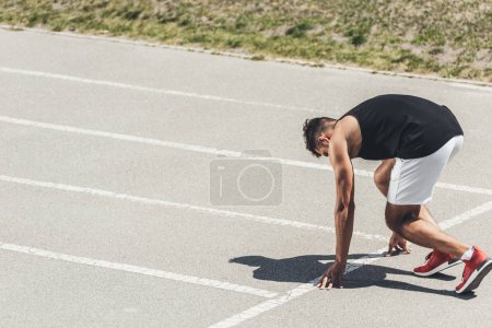 young male sprinter in starting position on running track