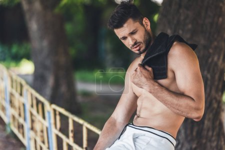 tired shirtless male athlete resting after workout with towel on shoulder