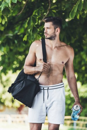 muscular young man with bag for sport equipment and fitness bottle walking under green tree