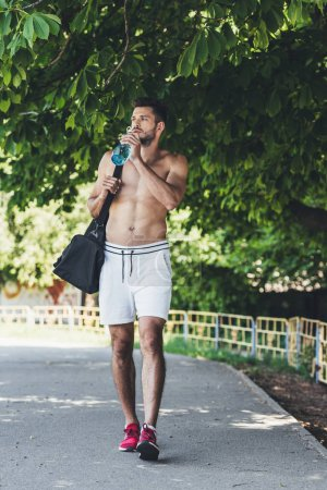 Photo for Attractive young man with bag for sport equipment drinking water from fitness bottle - Royalty Free Image