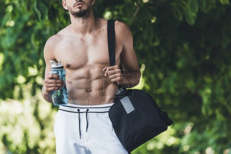 cropped shot of man with bag for sport equipment and fitness bottle