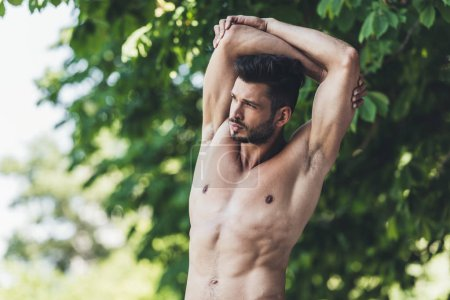 attractive shirtless young man stretching before workout in park