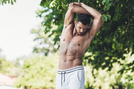 sporty shirtless young man stretching before workout in park