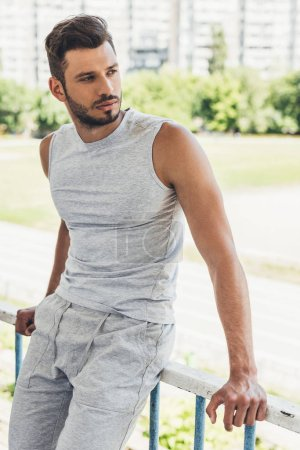 handsome young man in sportswear leaning on fence