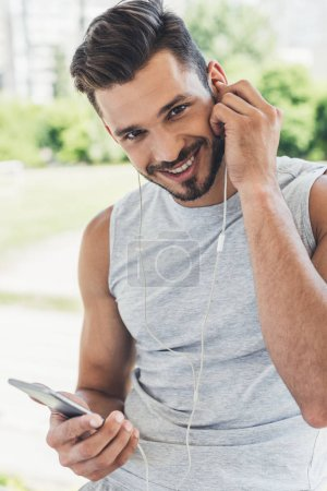 close-up portrait of happy young man listening music with smartphone and earphones and looking at camera outdoors