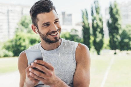 close-up portrait of handsome young man listening music with smartphone and earphones outdoors