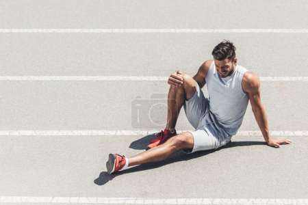 fit young jogger with leg injury sitting on running track
