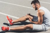 athletic young runner with leg injury sitting on floor of running track