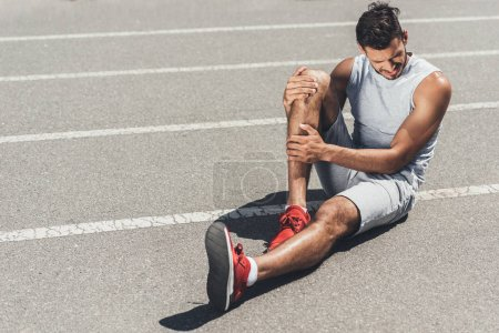 suffering young runner with leg injury sitting on floor of running track