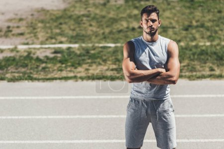 confident sporty young man with crossed arms looking at camera on running track
