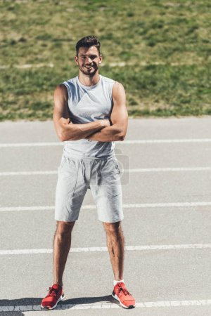 smiling sporty young man with crossed arms looking at camera on running track