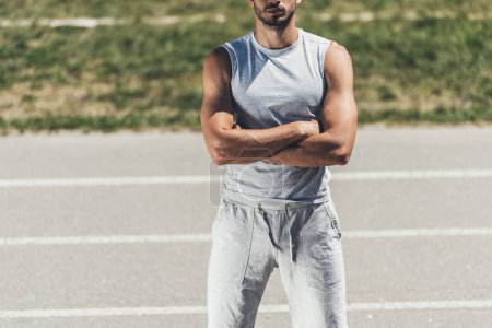 cropped shot of sporty young man with crossed arms on running track