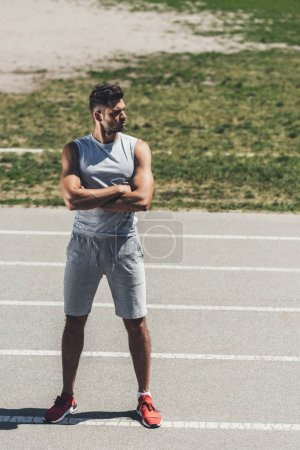 serious young man with crossed arms on running track